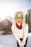 Mujer joven en vidrios de una Navidad delante de una casa de la montaña Imagen de archivo libre de regalías