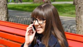 Mujer joven en vidrios que habla en el teléfono modile en un parque de la ciudad Muchacha que se sienta en un banco rojo al aire  almacen de metraje de vídeo