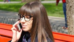 Mujer joven en vidrios que habla en el teléfono modile en un parque de la ciudad Muchacha que se sienta en un banco rojo al aire  metrajes