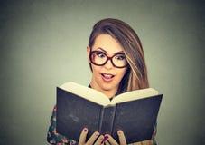 Mujer joven en vidrios que lee el libro grande Fotos de archivo libres de regalías