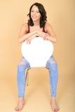 Mujer joven encantada feliz que se sienta en la risa blanca de la silla Fotografía de archivo libre de regalías