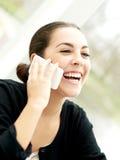 Mujer joven encantada que escucha una llamada de teléfono Imágenes de archivo libres de regalías