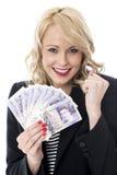 Mujer joven encantada que lleva a cabo moneda del dinero Foto de archivo