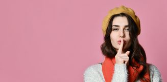 Mujer joven encantadora bonita que tiene finger secreto de la tenencia del rato en los labios y que muestra la muestra del silenc imagenes de archivo