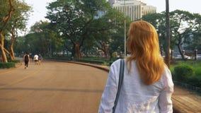 Mujer joven encantadora con el pelo de oro que acomete en el centro de ciudad almacen de metraje de vídeo