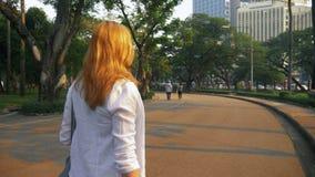 Mujer joven encantadora con el pelo de oro que acomete en el centro de ciudad metrajes