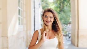 Mujer joven encantadora con a en un vestido blanco hermoso con la mujer joven del pelo flojo que camina en la calle, mirando la c almacen de video