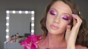 Mujer joven encantadora con maquillaje rosado almacen de video