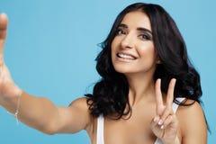 Mujer joven encantadora con sonrisa brillante vestida en el traje de baño blanco que toma el selfie en el fondo azul imagenes de archivo
