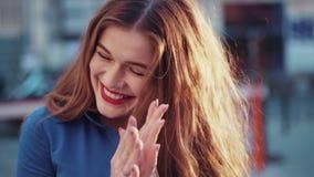 Mujer joven encantadora con un pelo de oro magnífico, ojos azules grandes, un lápiz labial rojo magnífico y una blusa azul elegan almacen de metraje de vídeo