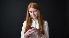 Mujer joven encantadora del jengibre en la camisa blanca que manda un SMS en el teléfono y que toca su pelo, aislado en fondo neg almacen de metraje de vídeo