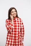 Mujer joven encantadora en la camisa larga de moda del control que hace phonecalls Imágenes de archivo libres de regalías