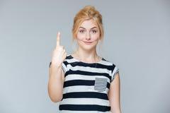 Mujer joven encantadora feliz que muestra un finger y que destaca Foto de archivo
