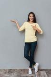 Mujer joven encantadora feliz que señala y que lleva a cabo el copyspace en la palma Imagen de archivo libre de regalías