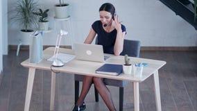 Mujer joven encantadora feliz que se sienta y que trabaja con el ordenador portátil usando las auriculares en oficina almacen de video