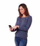 Mujer joven encantadora que manda un SMS en el teléfono móvil Imágenes de archivo libres de regalías
