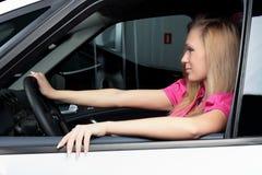 Mujer joven encantadora que se sienta en un coche Fotos de archivo