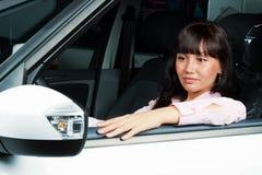 Mujer joven encantadora que se sienta en un coche Fotos de archivo libres de regalías