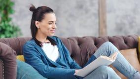 Mujer joven encantadora que sonríe y que lee el libro interesante que se sienta en posibilidad muy remota media del sofá almacen de video