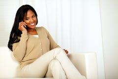 Mujer joven encantadora que sonríe y que conversa en el teléfono Foto de archivo