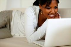 Mujer joven encantadora que sonríe y que mira a la computadora portátil Fotos de archivo libres de regalías