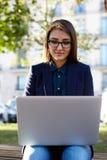 Mujer joven encantadora que usa el artilugio del ordenador portátil que se sienta al aire libre en el día hermoso soleado Foto de archivo libre de regalías