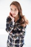 Mujer joven encantadora sonriente en la situación y la presentación de la camisa de tela escocesa Fotografía de archivo libre de regalías
