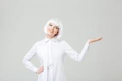 Mujer joven encantadora sonriente que coloca y que lleva a cabo el copyspace en la palma Fotos de archivo libres de regalías