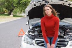 Mujer joven enfadada al lado de ella coche analizado Imagen de archivo libre de regalías