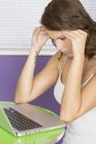 Mujer joven enfadada atractiva que comtempla la decisión usando el ordenador portátil Foto de archivo libre de regalías