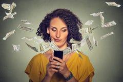 Mujer joven enfadada que usa smartphone con los billetes de dólar que se van volando Fotos de archivo