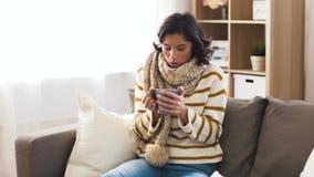 Mujer joven enferma en bufanda que bebe té caliente en casa metrajes