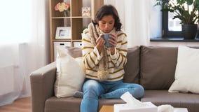 Mujer joven enferma en bufanda que bebe té caliente en casa almacen de metraje de vídeo