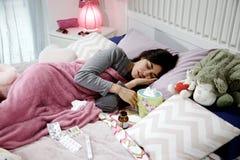 Mujer joven enferma enferma en cama con la medicina infeliz Imagen de archivo