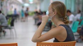 Mujer joven enferma que se sienta en la cita de un doctor que espera del hospital para metrajes