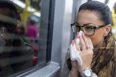 Mujer joven enferma que sopla su nariz Imagenes de archivo