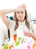 Mujer joven enferma que tiene fiebre el mentir en el sofá Imagen de archivo libre de regalías