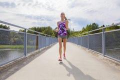 Mujer joven enfocada que corre en el puente sobre un lago Foto de archivo