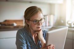 Mujer joven enfocada que trabaja en línea para su pequeña empresa imagen de archivo libre de regalías