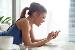 Mujer joven enojada confusa que tiene problema con smartphone en el hom Foto de archivo