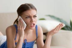 Mujer joven enojada que discute hablar en el teléfono celular en casa Fotos de archivo libres de regalías