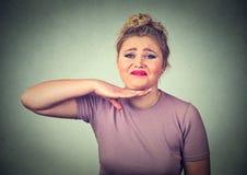 Mujer joven enojada que gesticula con la mano para parar el hablar Imagen de archivo libre de regalías