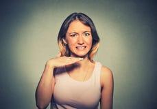 Mujer joven enojada que gesticula con la mano para parar el hablar, corte él hacia fuera Fotografía de archivo libre de regalías