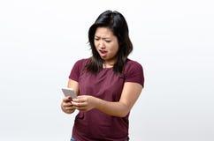 Mujer joven enojada que mira en su móvil Fotos de archivo libres de regalías