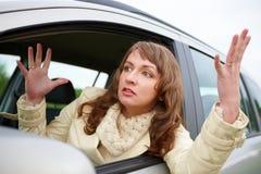 Mujer joven enojada que se sienta en un coche imagen de archivo
