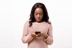Mujer joven enojada que sostiene su móvil Imagenes de archivo