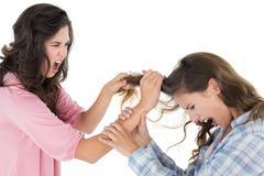Mujer joven enojada que tira del pelo de las hembras en una lucha imágenes de archivo libres de regalías