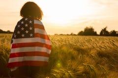 Mujer joven envuelta en bandera de los E.E.U.U. en campo en la puesta del sol Foto de archivo