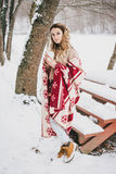 Mujer joven envuelta en la manta que bebe té caliente en bosque nevoso Foto de archivo libre de regalías