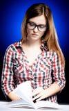 Mujer joven tranquila con los vidrios del empollón que aprende diligente Fotos de archivo libres de regalías